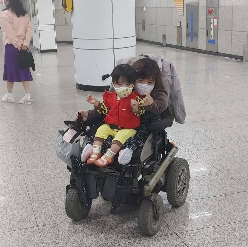 다음에 올 열차를 기다리며 딸과 지하철 나들이. 전동 휠체어에서 딸을 뒤에서 감싸 안는 형태로 함께 앉아 손하트를 한다. ⓒ이라나