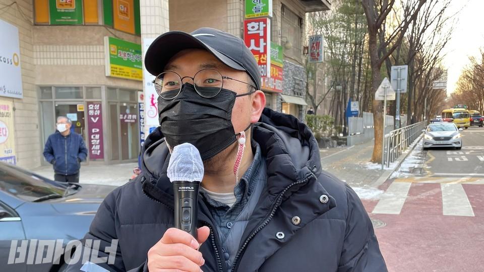 정민구 장애와인권발바닥행동 활동가가 기자회견에서 발언하고 있다. 까만색 모자와 마스크, 안경을 썼다. 사진 하민지