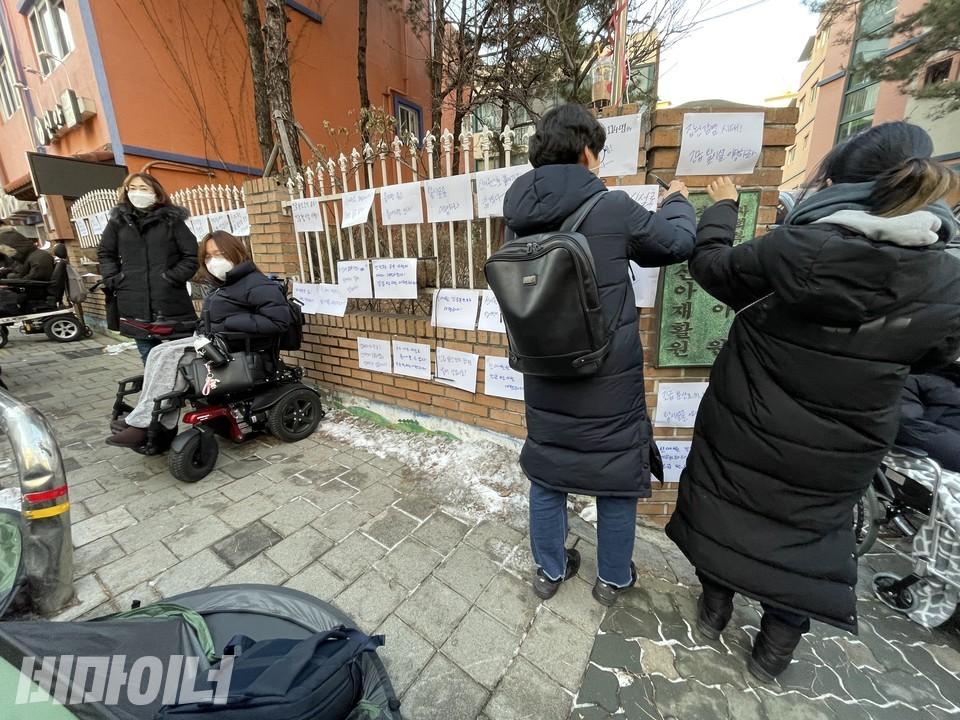 활동가들이 신아원 현판 주변에 피켓을 붙이고 있다. 사진 하민지