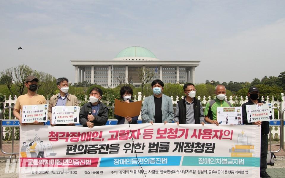 장애인권단체 소속 청각장애인 활동가들이 국회의사당 앞에서 기자회견을 열고 있다. 현수막에는'청각장애인, 고령자 등 보청기 사용자의 편의증진을 위한 법률개정 청원'이라고 적혀 있다. 사진 하민지