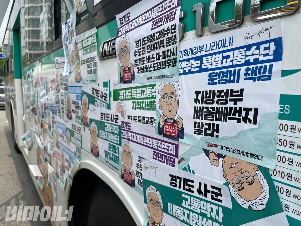 활동가들이 점거한 버스가 피켓으로 뒤덮여 있다. 피켓에는 이재명 지사 그림과 함께'경기도 교통약자이동편의증진조례 전면개정, 경기도특별교통수단 수도권 전체지역 운행, 경기도 버스 대폐차시 저상버스 도입 의무화' 등의 문구가 적혀 있다. 사진 하민지