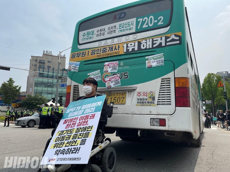 한 활동가가 버스를 점거했다. 목에 두른 피켓에는'모두가 평등하게 이동할 권리, 장애인 이동권 완전 실현, 경기도 장애인 이동권 증진을 위한 선언을 약속하라'라고 적혀 있다. 사진 하민지