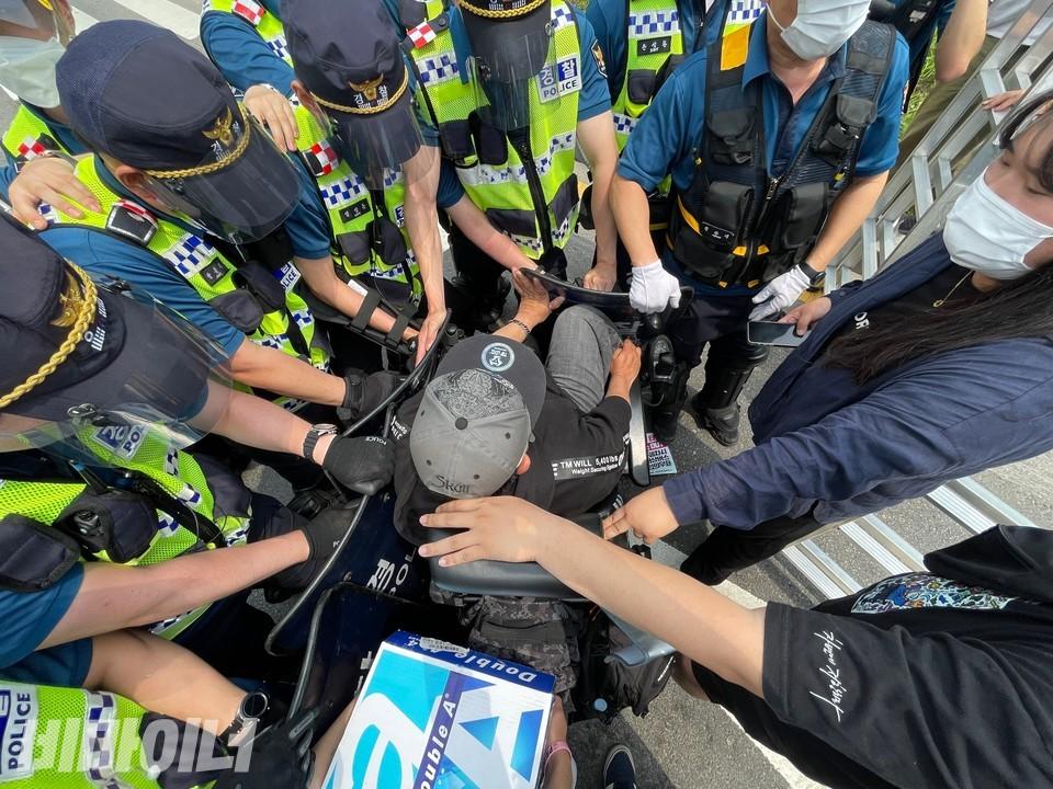 경찰 수십 명이 장애인 활동가 한 명을 막아서고 있다. 활동가는 팔과 다리로 경찰의 방패에 저항 중이다. 사진 하민지