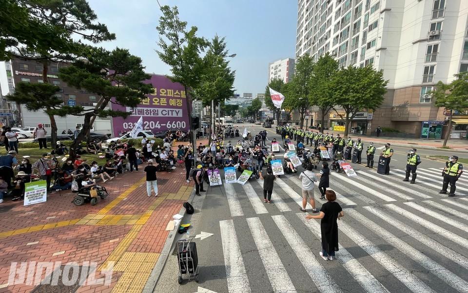 결의대회 모습. 왼쪽에 활동가 수십 명이 앉아 있고 오른쪽에 경찰이 줄지어 서 있다. 사진 하민지