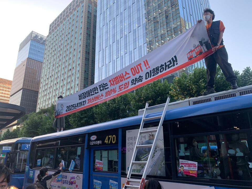 지난 6월 4일, 서울장차연 등 활동가들이 종로1가 버스정류장에서 470번 버스 위에 올라가 점거하고 있다.활동가들이 '비장애인만 타는 차별버스 OUT!! 2025년까지 저상버스 100% 도입 약속 이행하라'라고 적힌 현수막을 들고 있다. 사진제공 전국장애인차별철폐연대