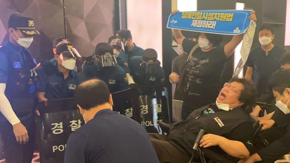 경찰이 휠체어 뒷부분을 강제로 낚아채서 휠체어가 뒤로 넘어질 뻔한 위험천만한 상황이 벌어졌다. 이에 깜짝 놀란 이형숙 회장이 비명을 지르고 있다. 사진 서울장애인차별철폐연대