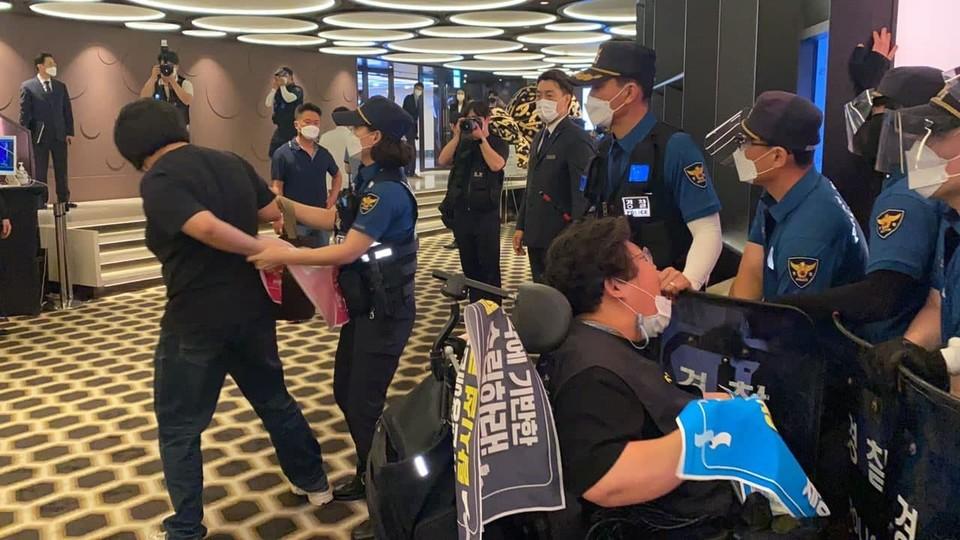 경찰이 활동가의 팔을 등 뒤에서 비틀어 붙잡으면서 강제 연행하고 있다. 사진 서울장애인차별철폐연대